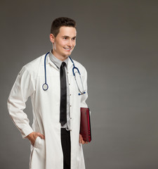 Smiling male doctor posing with red laptop