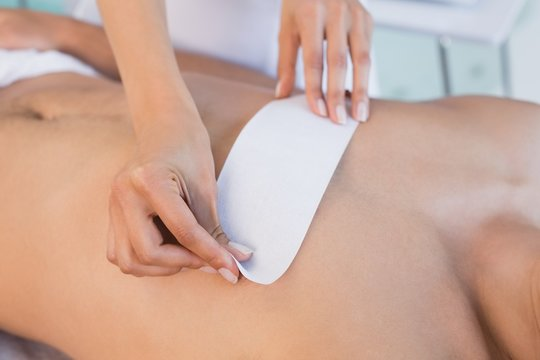 Beauty therapist waxing mans chest