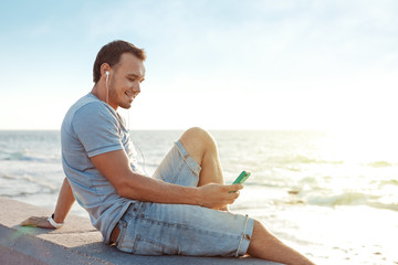 handsome man sitting near the sea with mobile smartphone