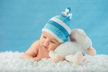 Child in hat hugging toy on a white bedspread, on a blue backgro