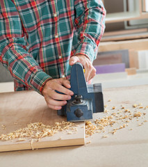 Midsection Of Carpenter Working With Electric Planer