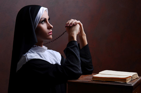 Young attractive nun praying