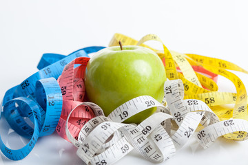 Colorful measuring tapes with green apple