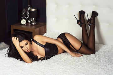 Sexy brunette woman in bed