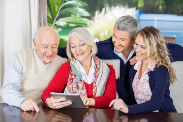 Grandchildren Looking At Grandparents Using Digital Tablet