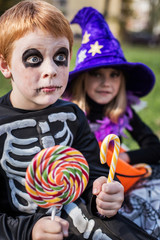Halloween. Skeleton and witch holding colorful candies