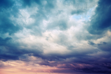 Dark blue stormy cloudy sky natural photo background, toned