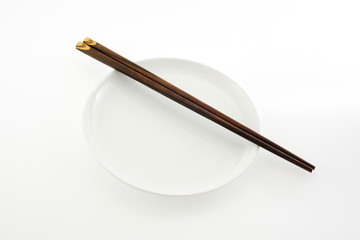 white plate with chopsticks isolated on white background