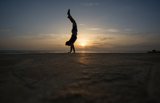 silhouetted man doing handstand in sunset
