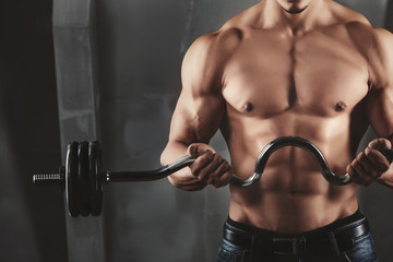 Close up of young muscular man lifting weights