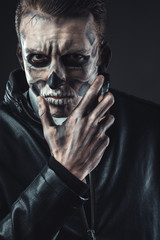 Portrait of pensive man with make-up  skull
