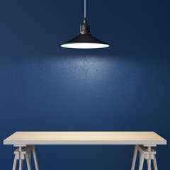 Table and lamp near blue wall