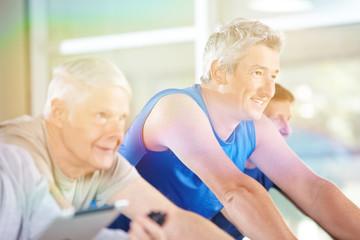 Senioren trainieren beim Spinning im Fitnesscenter