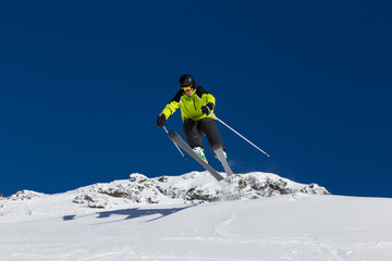 Alpine skier jumping from hill