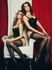 two sexy women in lingerie on white throne