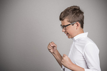 side portrait angry young man fists up in air grey background