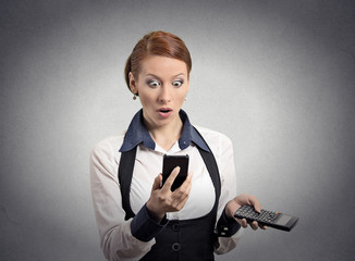 Shocked female looking on smart phone holding calculator
