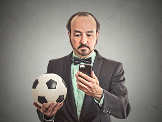 business man watching football game on smartphone