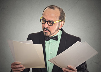 Confused businessman looking at documents papers contracts