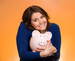 woman holding piggy bank isolated on orange background