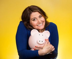 Happy woman holding piggy bank isolated on yellow background