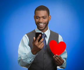 Man looking at smart phone holding red heart blue background