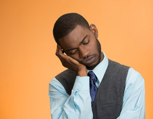 sleepy tired young business man on orange background