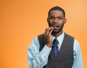 Man with toothache touching face isolated on orange background