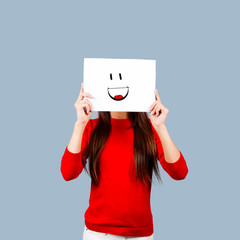 Girl holding a paper with a happy face painted Isolated on White