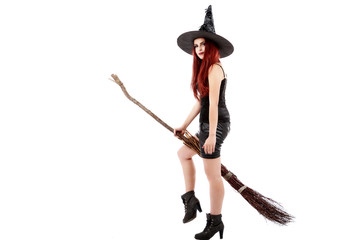 happy young witch with a broom, isolated on white studio backgro