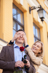 girl covering her boyfriend's eyes to surprised him.