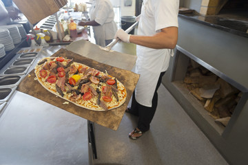 Chef holding pizza on spatula in kitchen