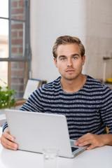 junger mann mit laptop in seinem apartment