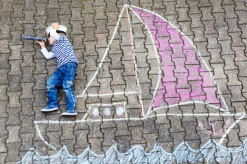 Little boy having fun with ship picture drawing with chalk