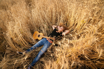 girl with a guitar lying in the wheat field, view from above