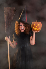 Woman dressed like a witch and holding broom and pumpkin.