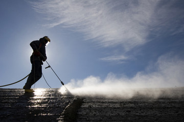 Worker on top of factory hall, with high pressure washer