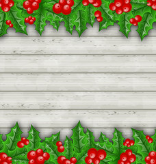 Christmas decoration holly berry branches on wooden background