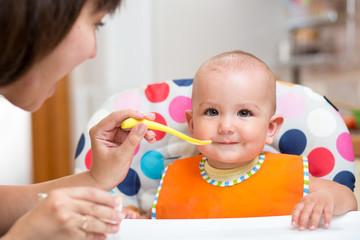 mother feeding baby  on kitchen