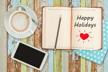 """Happy Holidays""on notebook with smart phone and coffee cup"