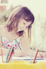 Beautiful smiling little  girl drawing and daydreaming at home