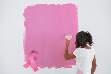 Composite image of young woman painting her wall in pink