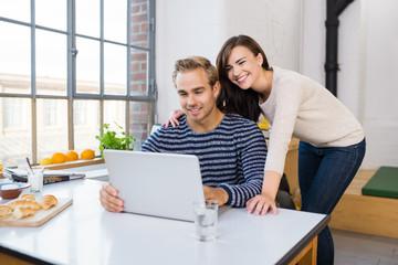 glückliches junges paar schaut auf laptop