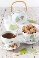tea on cup with teapot and amaretti sweets on white table