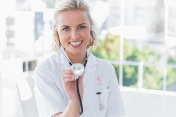 Composite image of radiant nurse showing her stethoscope