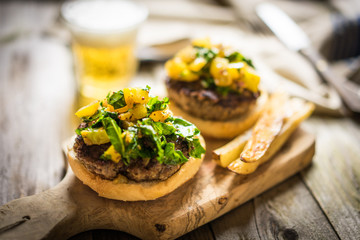 Homemade burgers with fries on wooden background