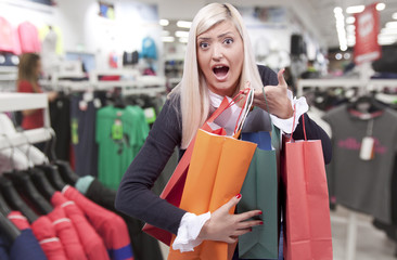 Smiling young blond woman in clothing store
