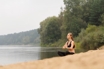 young beautiful woman practicing yoga at forest lake