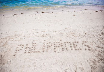 Philippines written in a sandy tropical beach