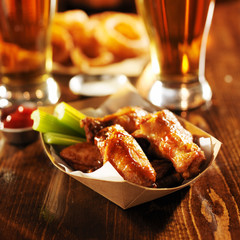 barbecue buffalo chicken wings served with beer, celery,